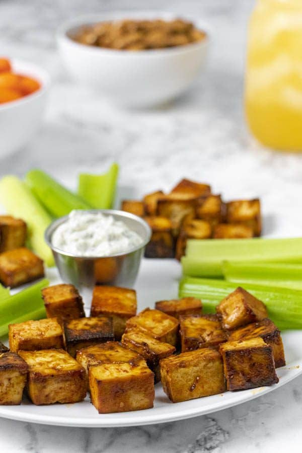 white serving dish of cooked tofu with celery and ranch on a party table