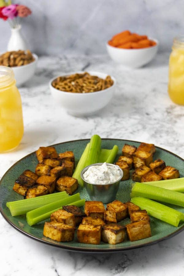 teal serving dish with tofu bites on a table with other party food and drinks