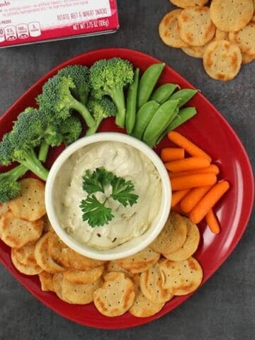 vegan onion dip on a serving platter with crackers and veggies to dip