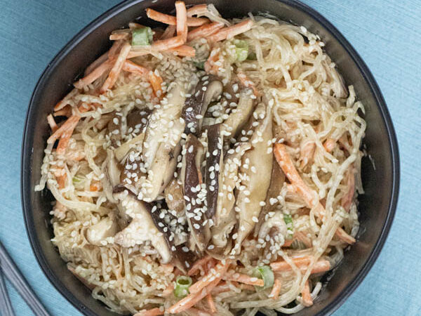 kelp noodle salad with carrots and green onions topped with shiitake mushrooms in a bowl