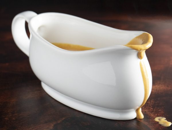 gravy boat on a wooden table with gravy dripping over the spout, so you can see the thickness