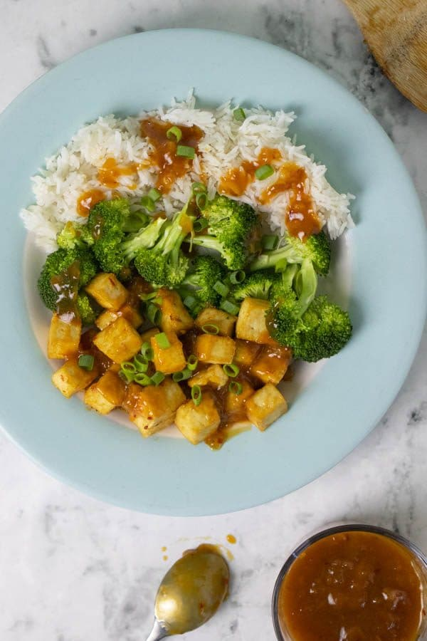 overhead photo of General Tso's Tofu on a blue plate with rice and broccoli
