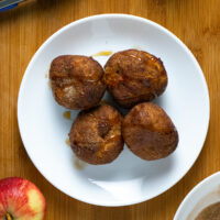 white plate of air fryer apple fritters with maple syrup and cinnamon sugar on top