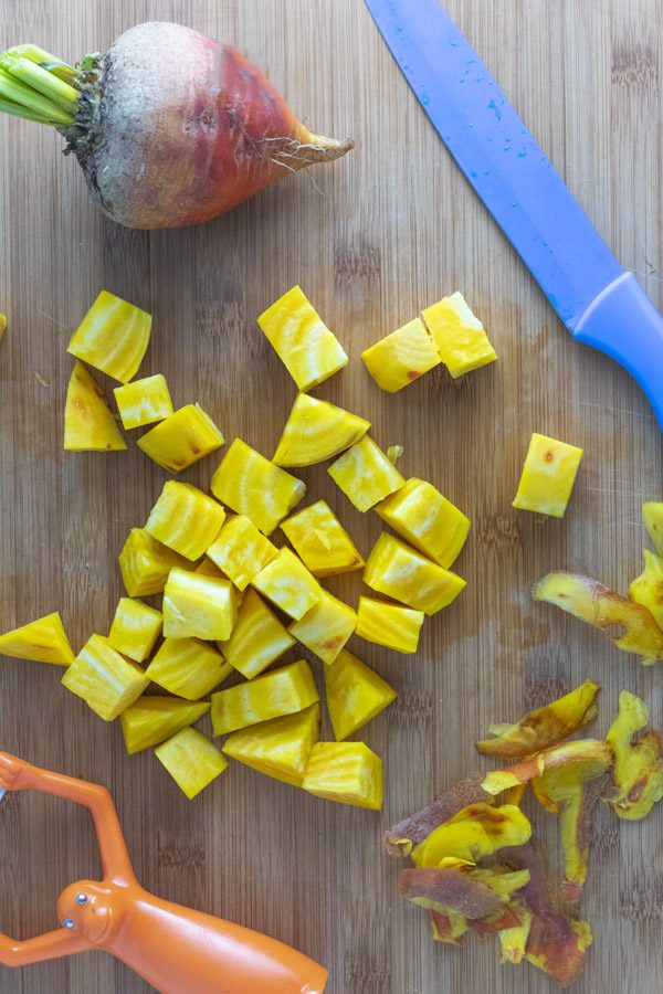 peeled and chopped golden beets on a wooden cutting board