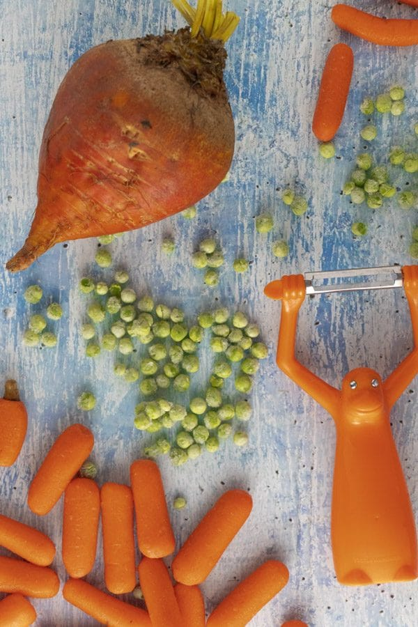 kid-friendly vegetables on a blue tabletop: beets, carrots, and peas