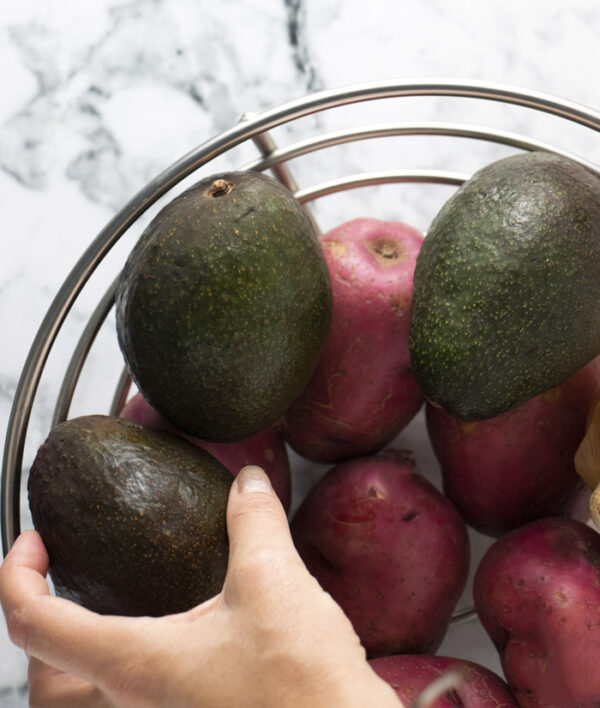 pulling ripe avocados out of a produce bowl