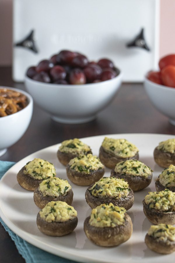 vegan stuffed mushrooms on a serving plate with other appetizers around it