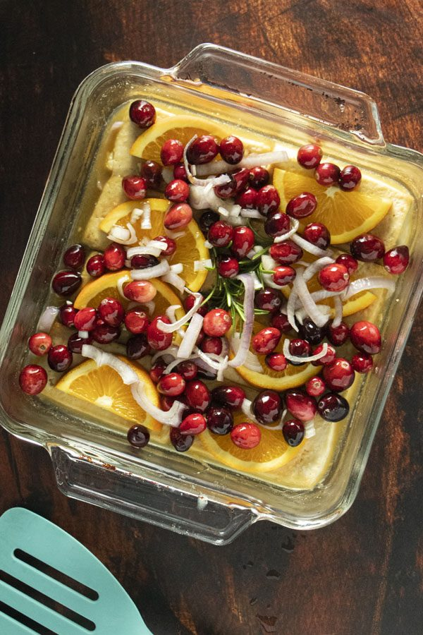glass baking tray with tofu, orange, rosemary, and cranberries in it