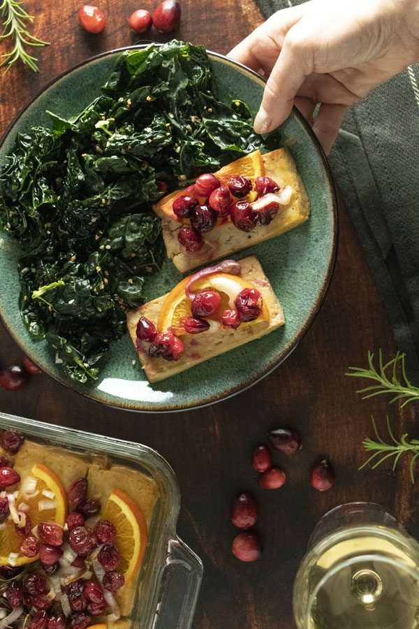 hand placing a plate of holiday tofu on a table with rosemary and fresh cranberries scattered on the table