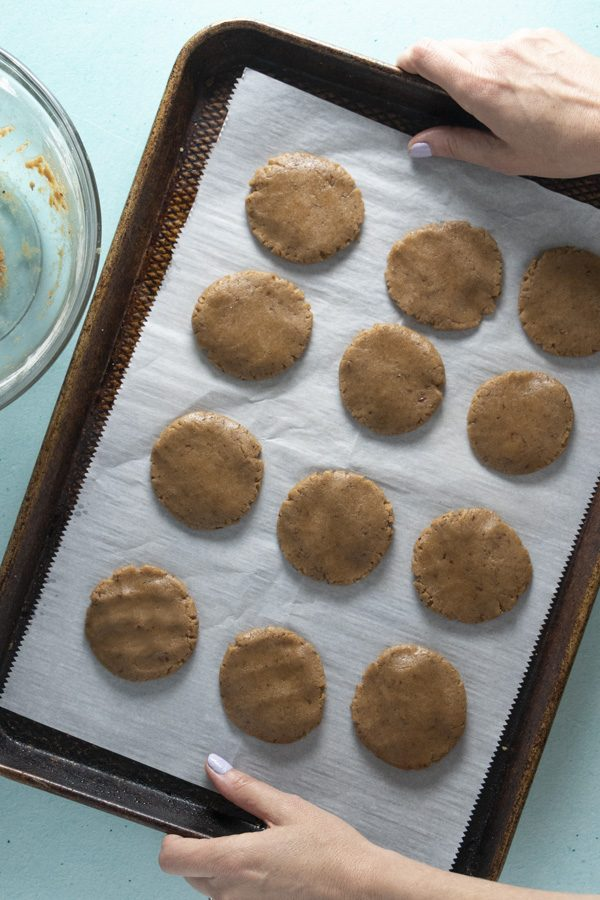 raw vegan brown sugar cookies on a baking sheet, ready for the oven