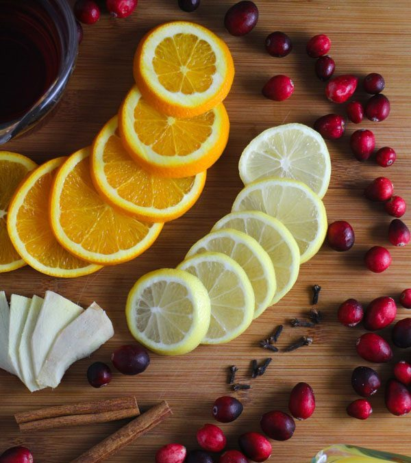 cranberry mulled wine ingredients on a large wooden cutting board