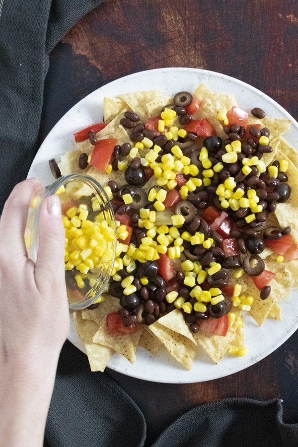 adding corn to a plate of chips with tomatoes, black beans, and olives on it