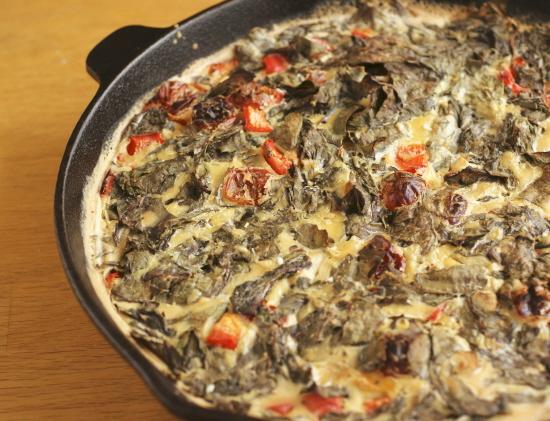 "closeup of a creamy chickpea ""quizza"" in a pan"