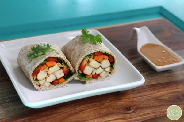 Cadry's Kitchen's spring roll wraps on a plate next to a dish of spicy peanut sauce