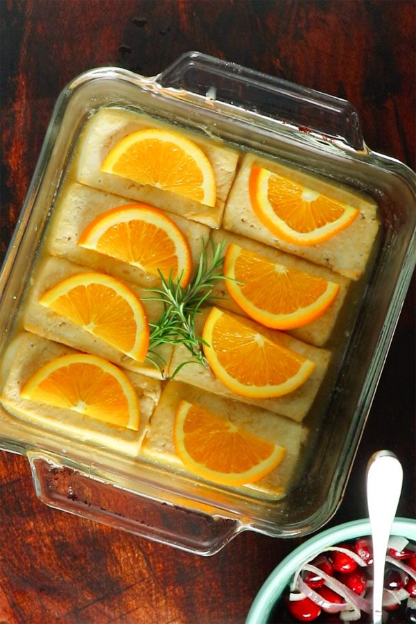 a glass baking pan with tofu topped with orange slices and rosemary