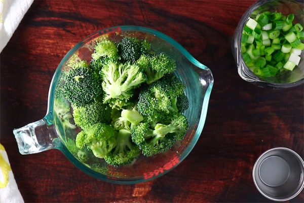 uncooked broccoli in a glass measuring bowl