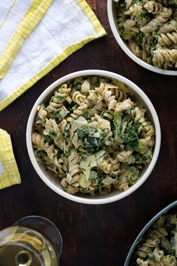 bowls of vegan pasta with spinach and artichoke cream sauce next to a glass of wine