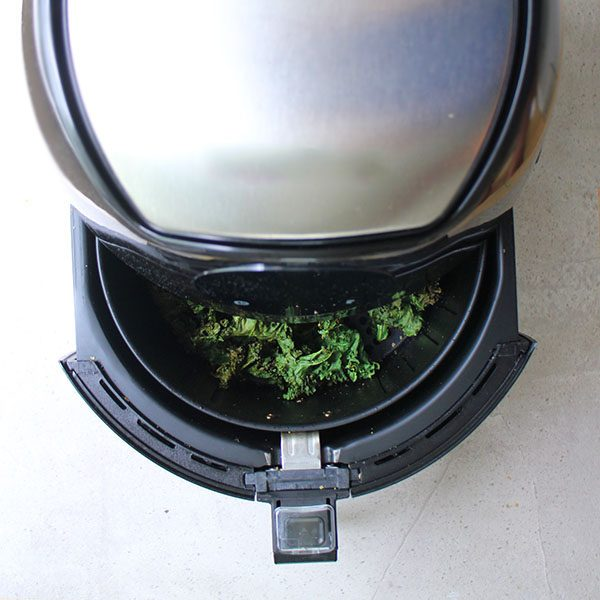 overhead photo of an air fryer opening up with kale chips inside