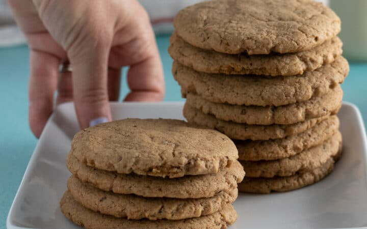 hand putting a plate of vegan brown sugar cookies on a blue tabletop