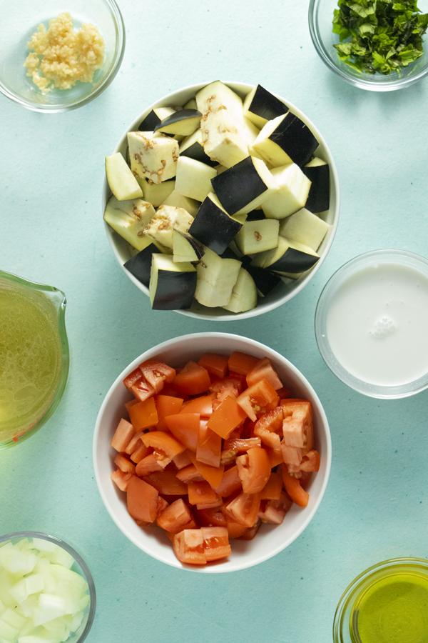 mise en scene of soup ingredients in bowls on a blue table
