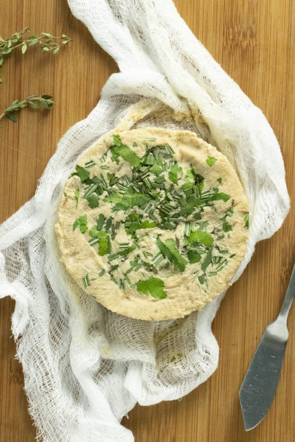 herb and roasted garlic vegan cream cheese unwrapped on a piece of cheesecloth