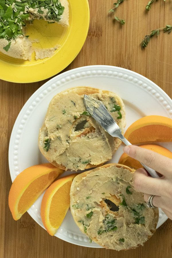 spreading vegan cream cheese with herbs and roasted garlic onto bagels on a plate with orange slices