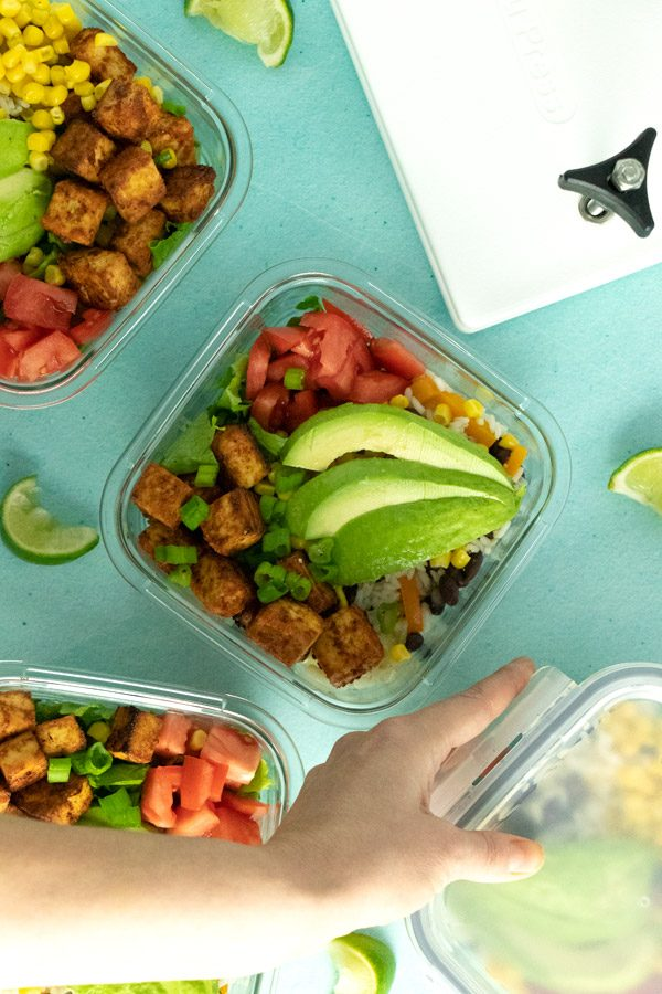 tofu burrito bowls in meal prep containers with the EZ Tofu Press next to them