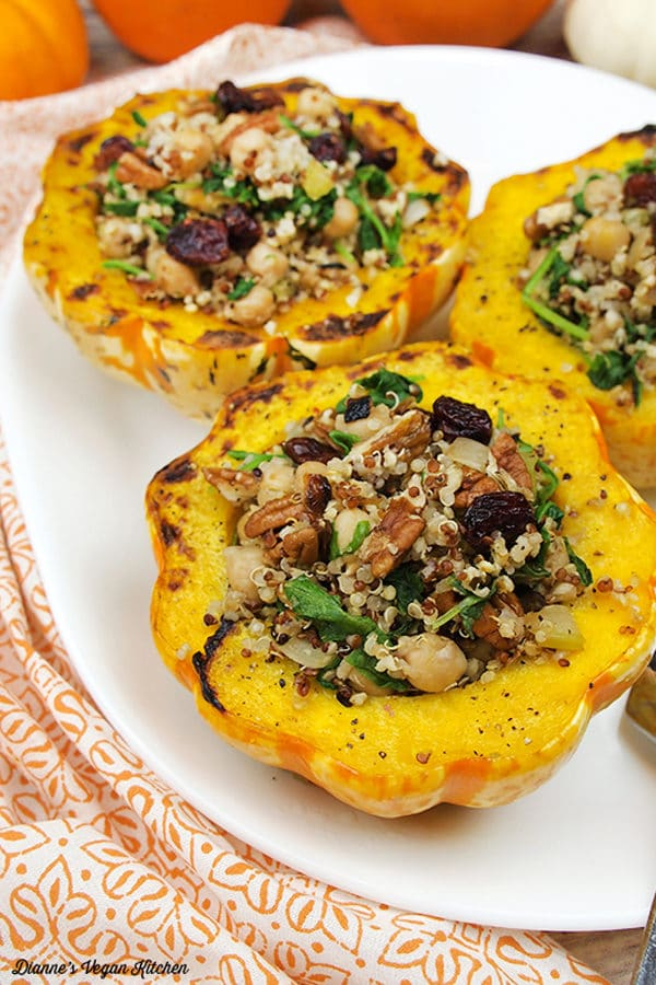 plate of 3 stuffed squash with quinoa, cranberries, and vegetables