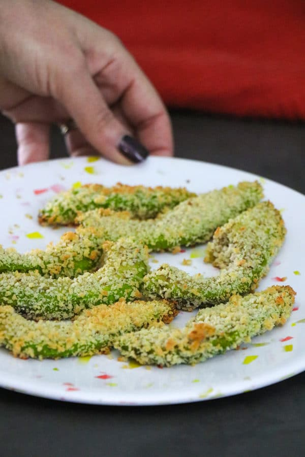 hand placing a plate of air fryer avocado fries onto a slate tabletop