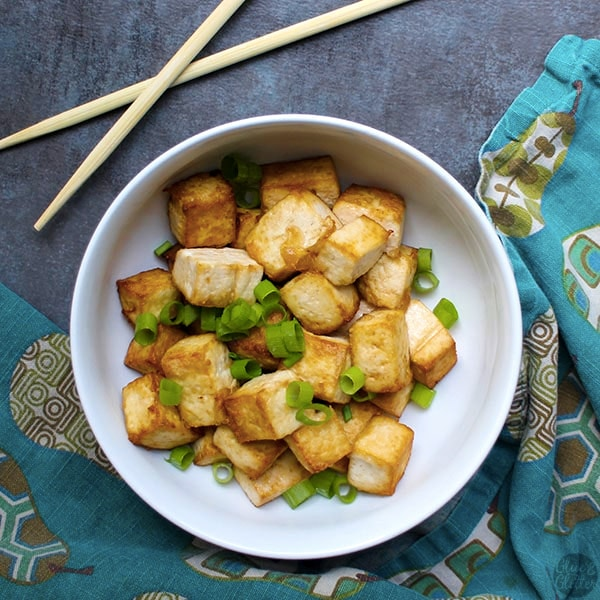 overhead photo of air fryer tofu in a white bowl with green onions
