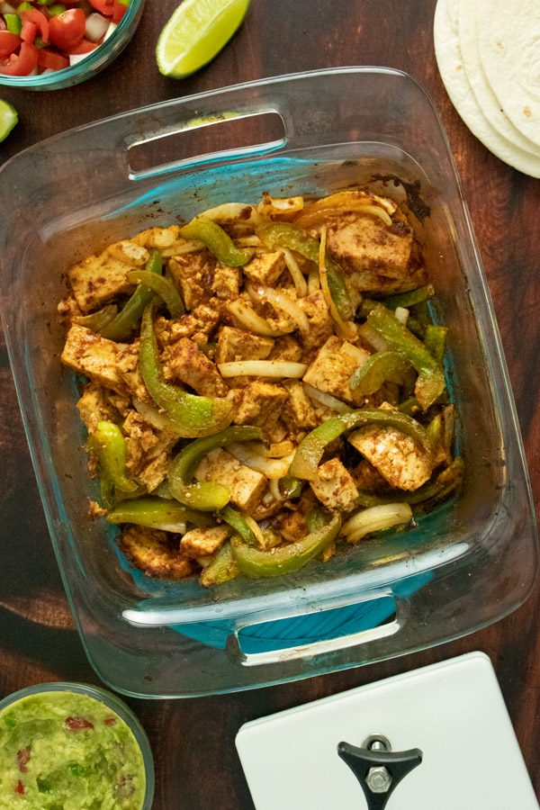 baked tofu fajitas with green peppers and onions, fresh out of the oven, in a glass pan