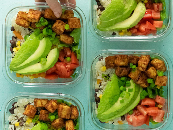 meal prep containers filled with tofu, beans and rice, and vegetables