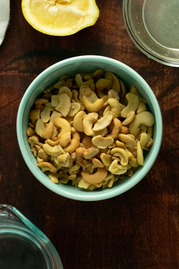 blue bowl of cashews on a wooden table with lemons, water, and lemon juice around it