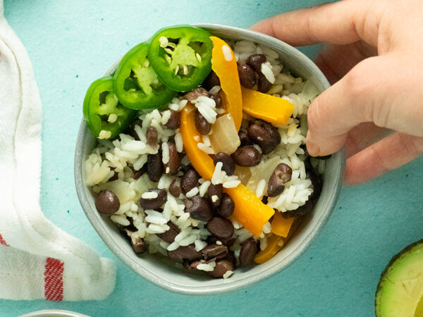 hand serving a bowl of vegan black beans and rice with bell peppers and sliced jalapeno