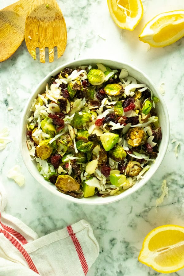 overhead photo of the brussels sprout salad in a white bowl with cranberries, almonds, and avocado