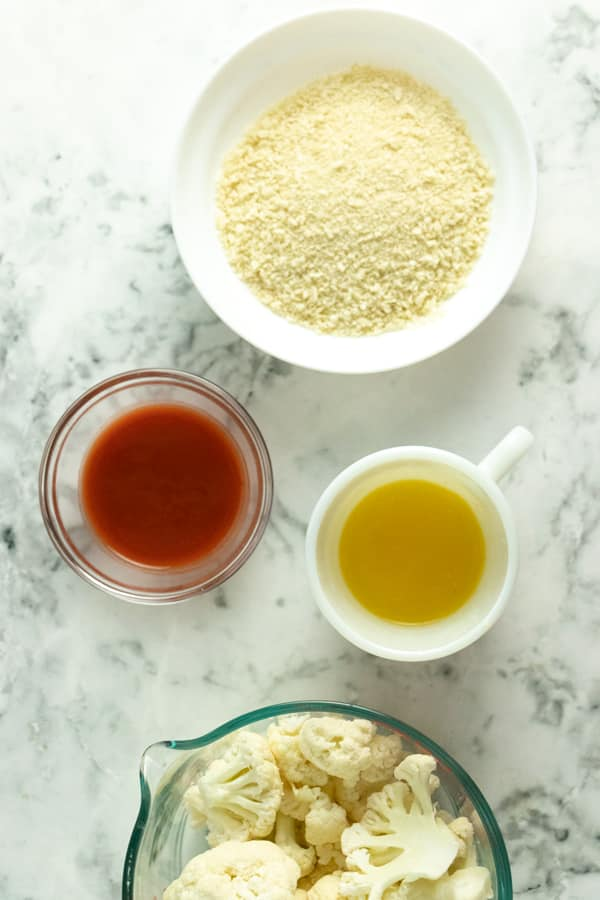 marble table with bowls of panko, cauliflower, and buffalo sauce and a mug of melted vegan butter