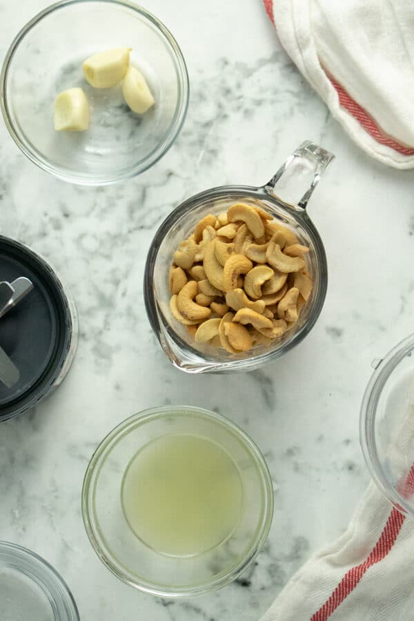 measuring cup of cashews with cups of water, lemon juice, and garlic next to it on a marble tabletop
