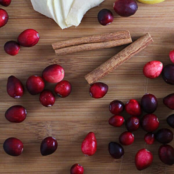 cranberry recipe ingredients on a wooden cutting board: cinnamon sticks, ginger, and fresh cranberries