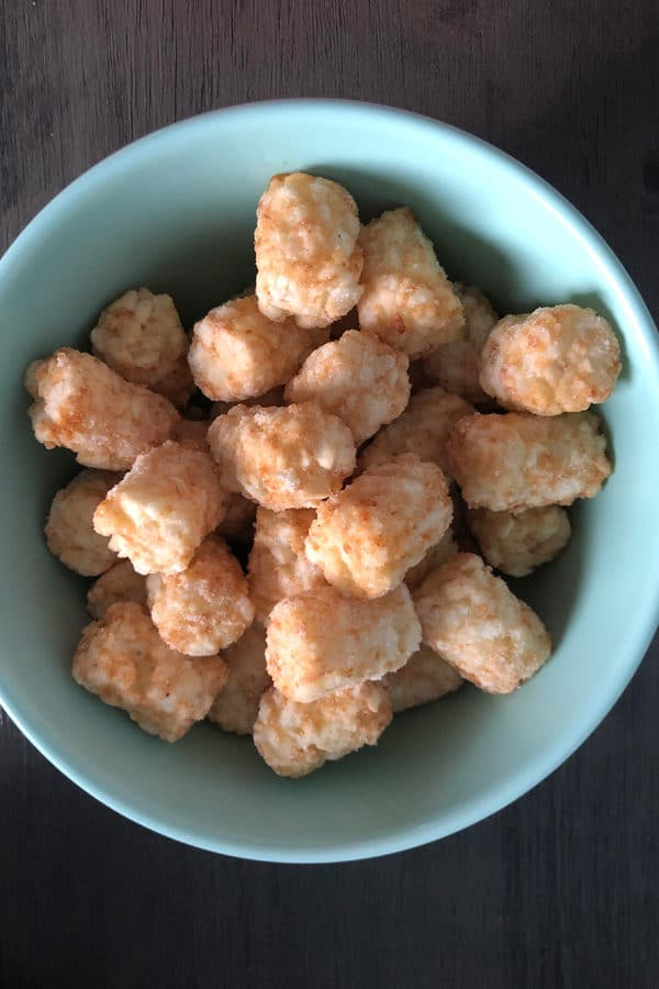 frozen tater tots in a blue bowl