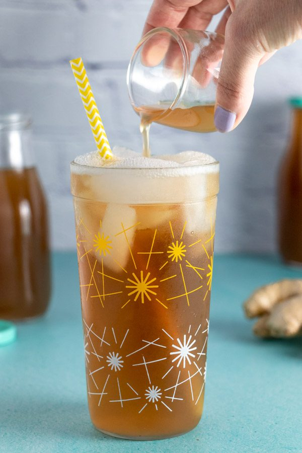 pouring syrup into a glass to make homemade ginger ale