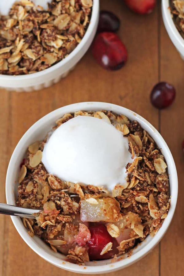 bowl of pear cranberry crisp topped with vegan vanilla ice cream