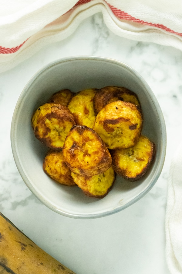 gray bowl of cooked air fryer plantains on a marble tabletop