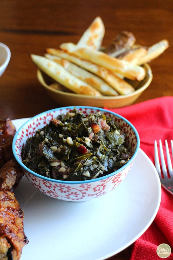 red and white bowl of collard greens with a bowl of fries in the background
