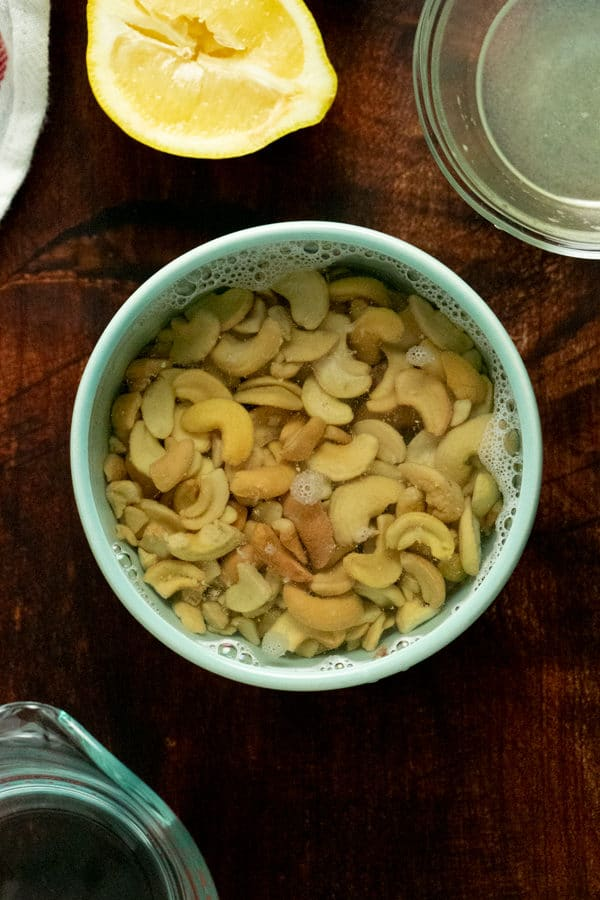 cashews soaking in a blue bowl of hot water