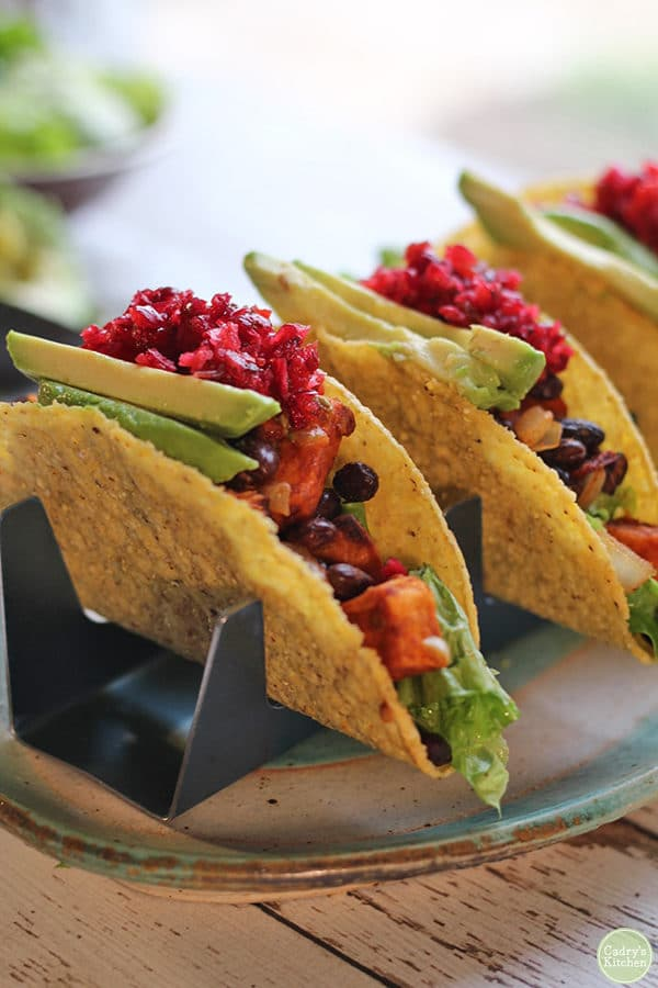 taco holder with 3 hard-shell tacos with cranberry salsa on top