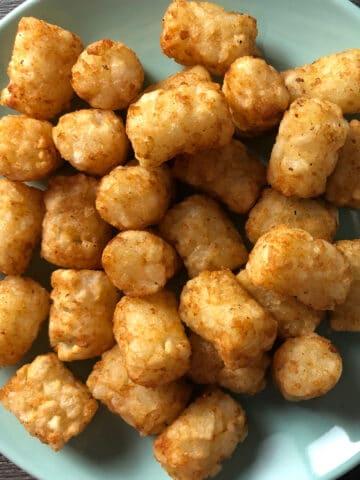 overhead photo of crispy tots on a blue plate