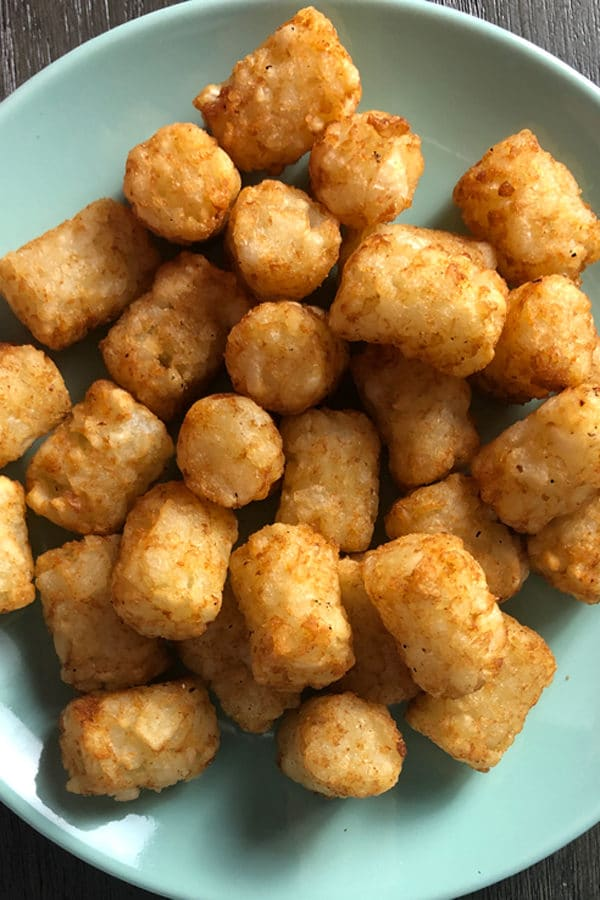 close-up of crispy tater tots on a blue plate