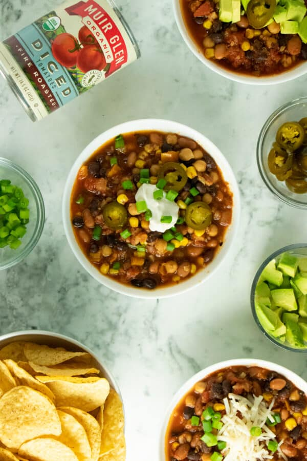 overhead photo of bowls of 3-bean chili with different toppings