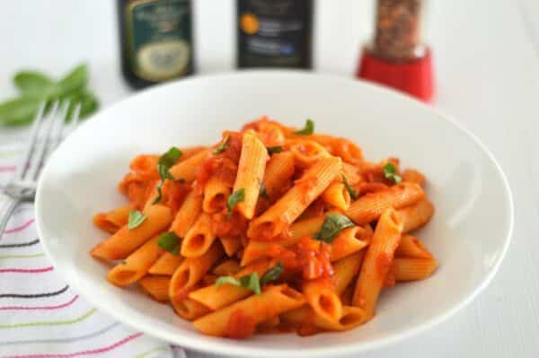 white bowl of Penne all'Arrabbiata with fresh basil on top