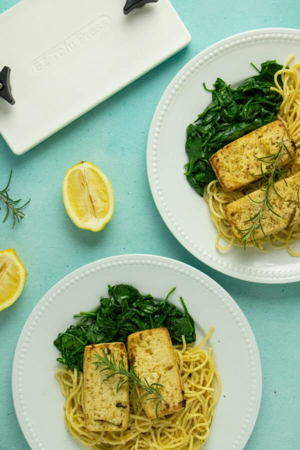 plates of the tofu on a bed of pasta and spinach next to the EZ Tofu Press